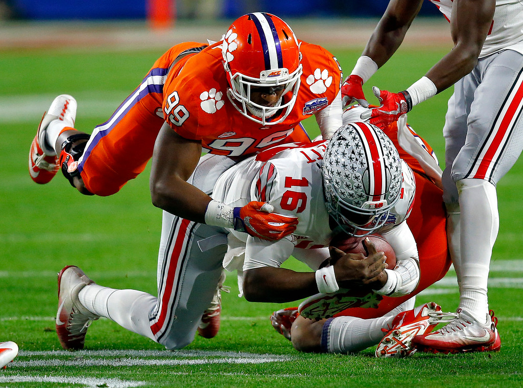 . Ohio State quarterback J.T. Barrett (16) is hit by Clemson safety Van Smith and defensive end Clelin Ferrell (99) during the first half of the Fiesta Bowl NCAA college football playoff semifinal, Saturday, Dec. 31, 2016, in Glendale, Ariz. (AP Photo/Ross D. Franklin)