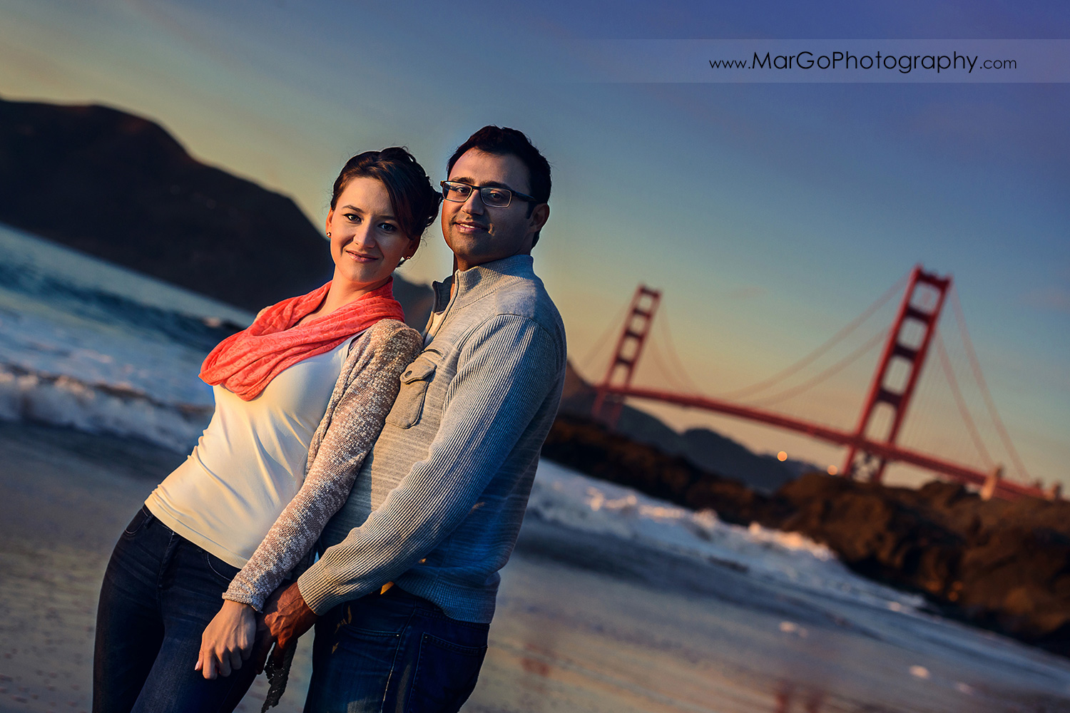 3/4 portrait of man and woman in grey sweater and jeans sitting on the sand with Golden Gate Bridge in background during engagement session at San Francisco Baker Beach