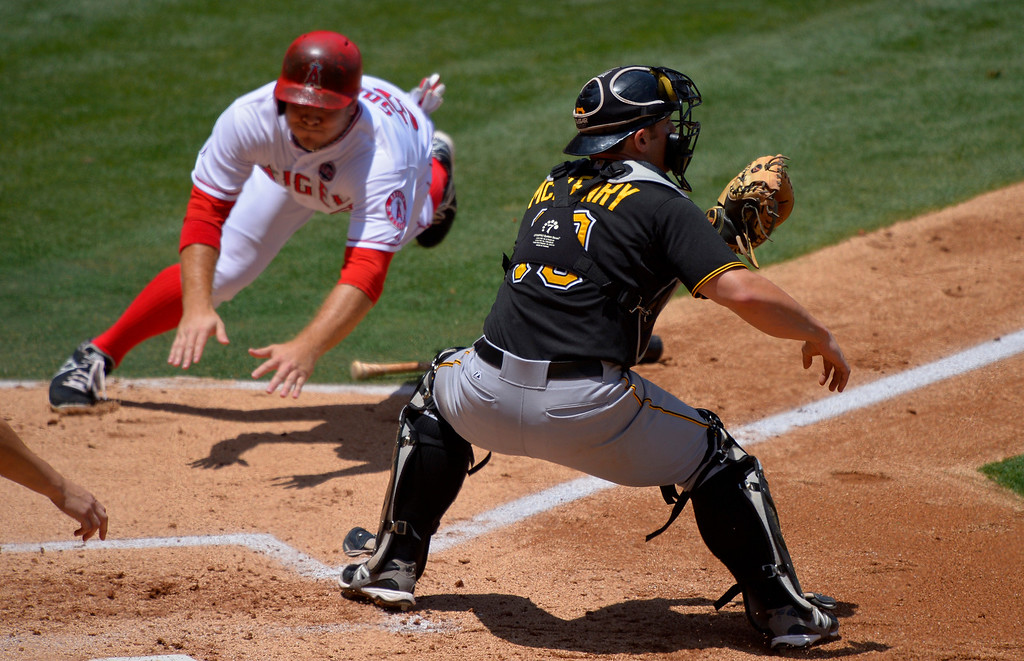 . Los Angeles Angels\' J.B. Shuck, left scores on a fielders choice by Mike Trout as Pittsburgh Pirates catcher Michael McKenry takes a late throw during the second inning of their baseball game, Sunday, June 23, 2013, in Anaheim, Calif.  (AP Photo/Mark J. Terrill)