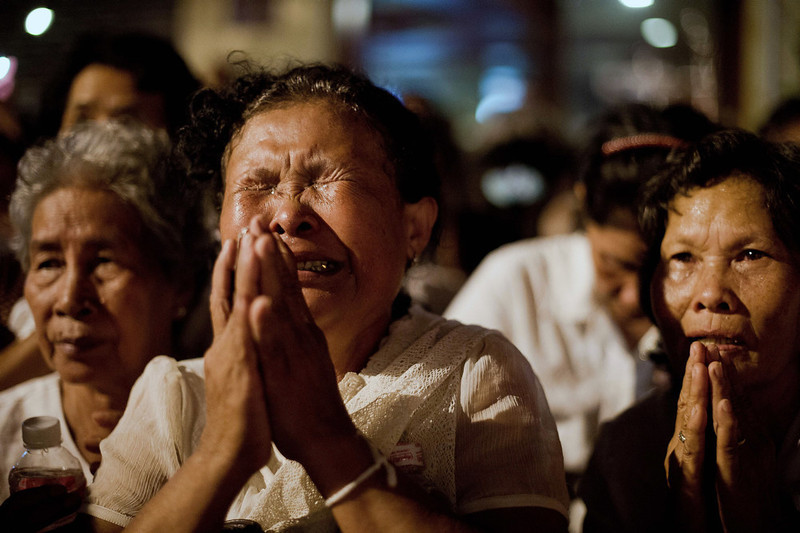 . Cambodian mourners cry as smoke rises out from the roof the crematorium during the cremation where a coffin bearing the remains of Cambodia\'s late King Norodom Sihanouk is placed, near the Royal Palace in Phnom Penh on February 4, 2013. Thousands of mourners massed in the Cambodian capital as the kingdom cremated its revered former King Norodom Sihanouk, who steered his country through six turbulent decades. AFP PHOTO/ Nicolas  ASFOURI/AFP/Getty Images