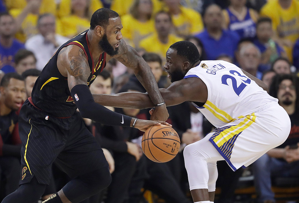 . Cleveland Cavaliers forward LeBron James, left, drives against Golden State Warriors forward Draymond Green during the first half of Game 1 of basketball\'s NBA Finals in Oakland, Calif., Thursday, May 31, 2018. (AP Photo/Marcio Jose Sanchez)