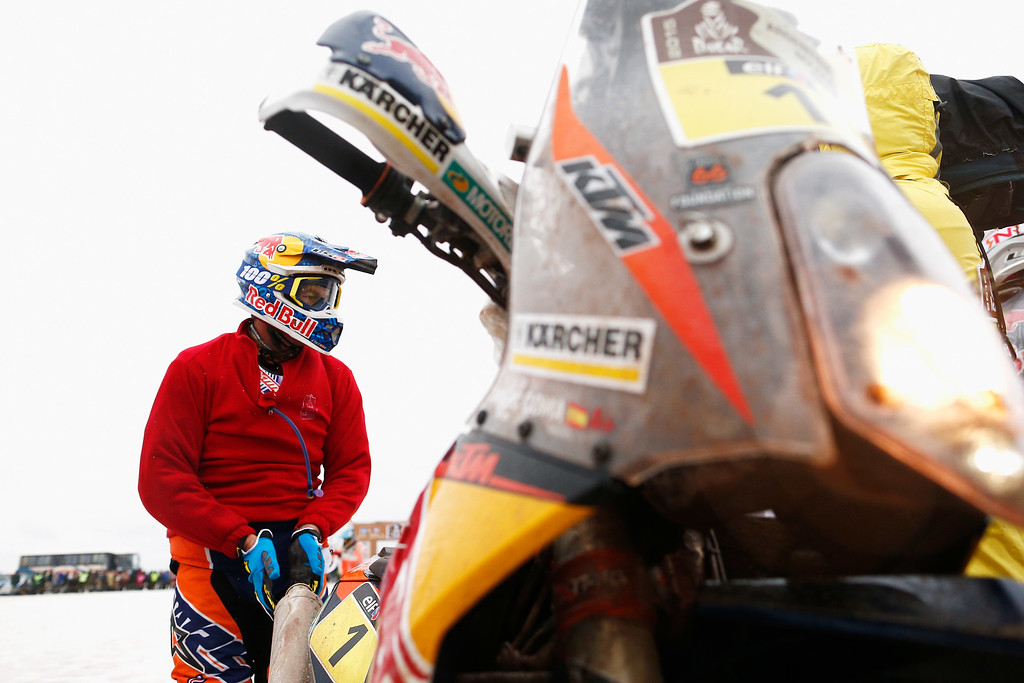 . UYUNI, BOLIVIA - JANUARY 12:  #1 Marc Coma of Spain and riding the for the Red Bull KTM Factory Team warms his hands on the exhaust as he waits on the start line during day 9 of the Dakar Rally on the Salar de Uyuni or Uyuni Salt Flats on January 12, 2015 in Uyuni, Bolivia.  (Photo by Dean Mouhtaropoulos/Getty Images)