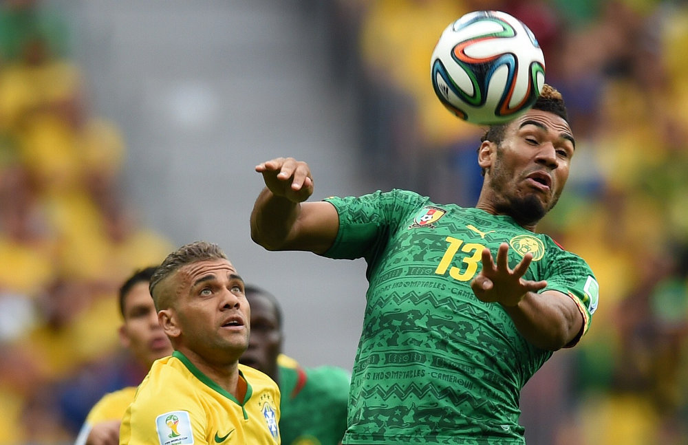 . Cameroon\'s forward Eric Maxim Choupo-Moting (R) heads the ball next to Brazil\'s defender Dani Alves during a Group A football match between Cameroon and Brazil at the Mane Garrincha National Stadium in Brasilia during the 2014 FIFA World Cup on June 23, 2014.    PEDRO UGARTE/AFP/Getty Images