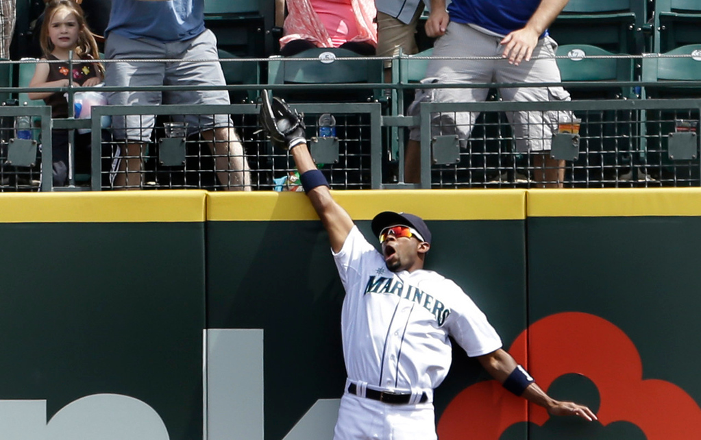 . Mariners right fielder Endy Chavez leaps above the wall to snag a deep fly ball off the bat of Minnesota\'s Chris Colabello in the third inning. (AP Photo/Elaine Thompson)