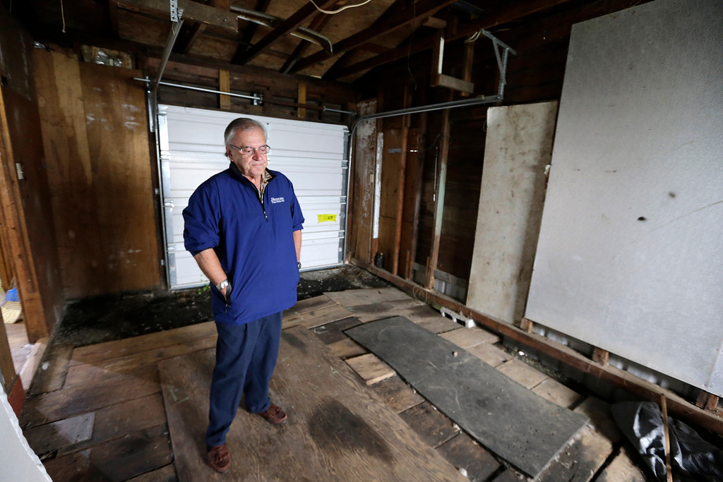 . In this photo taken Monday, Sept. 23, 2013, Dann Sears, curator of the Aberdeen Museum of HIstory, stands in the tiny garage of the childhood home of Kurt Cobain, the late frontman of Nirvana, in Aberdeen, Wash. (AP Photo/Elaine Thompson)