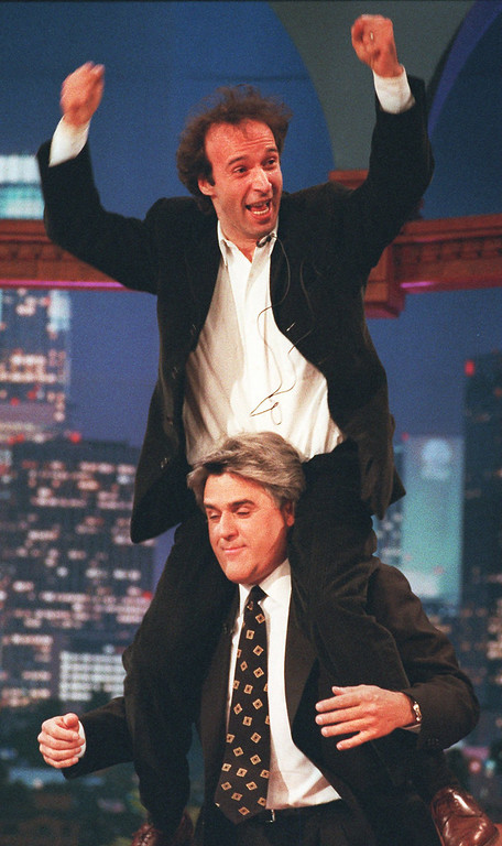 """. Italian comedian Roberto Begnini gets a ride on the shoulders of late night talk show host Jay Leno during taping of \""""The Tonight Show\"""" at the NBC studios in Burbank, Calif., Thursday, April 18, 1996. (AP Photo/The Tonight Show)"""