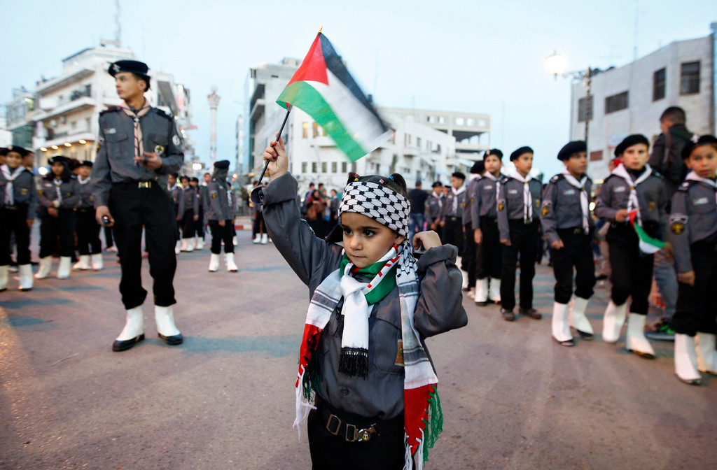 . A Palestinian girl waves a flag during a rally supporting the Palestinian U.N. bid for observer state status, in the West bank city of Ramallah, Thursday, Nov. 29, 2012. The Palestinians are certain to win U.N. recognition as a state on Thursday but success could exact a high price: delaying an independent state of Palestine because of Israel\'s vehement opposition. (AP Photo/Majdi Mohammed)