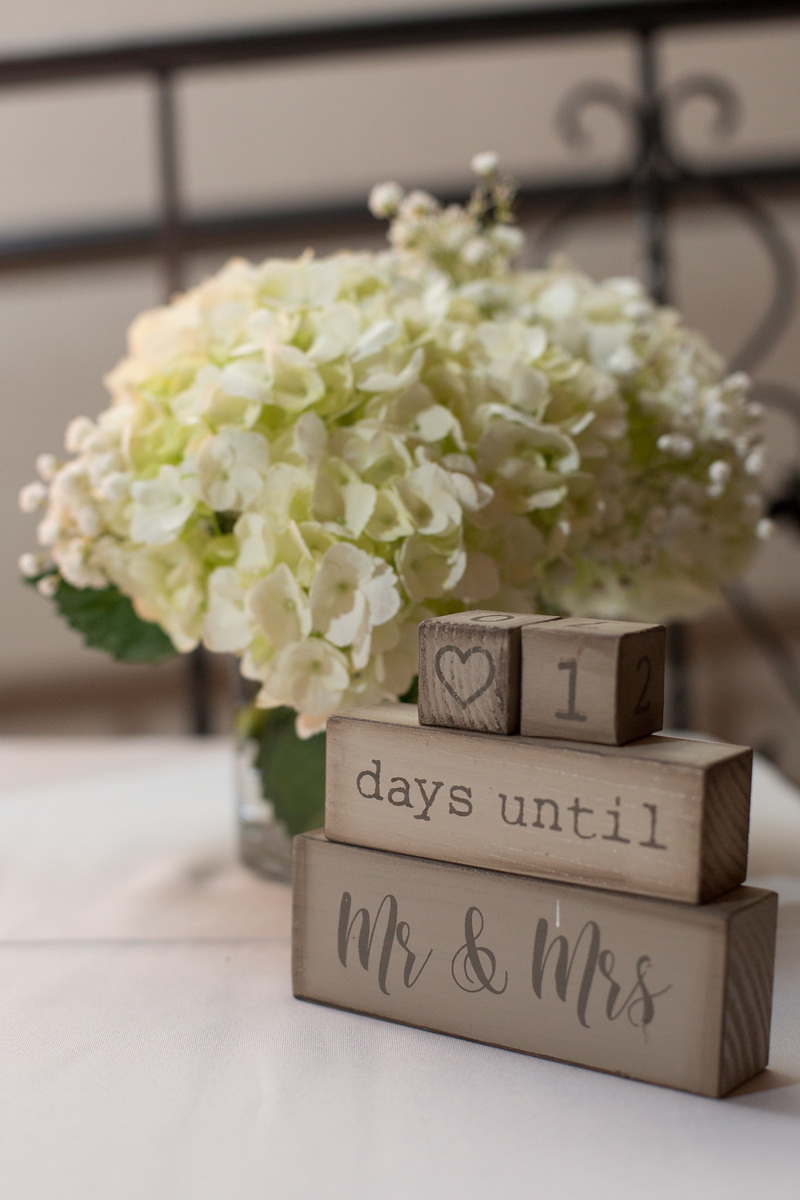 Wedding countdown blocks in front of a vase of white flowers