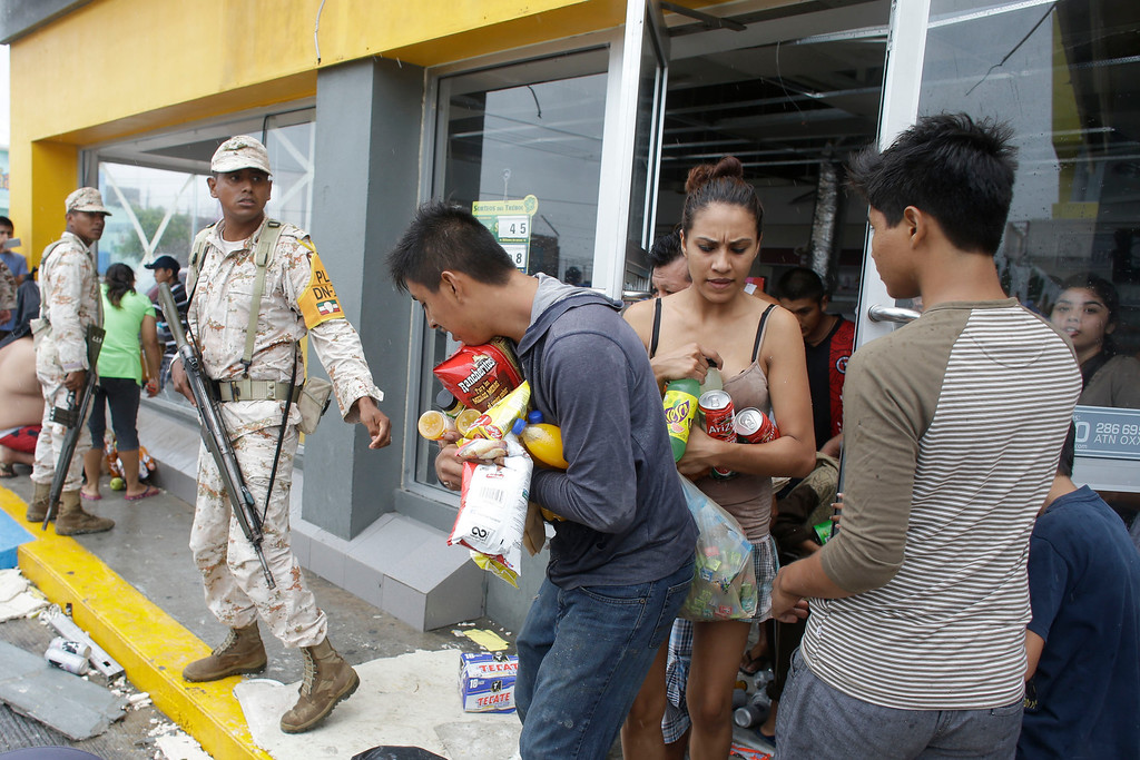 . Mexican soldiers try to stop people from looting a convenience store destroyed by Hurricane Odile,  in Los Cabos, Mexico, Monday, Sept. 15, 2014. The storm, which made landfall near Cabo San Lucas the previous night as a powerful Category 3 hurricane, toppled trees, power poles and road signs along the main highway, which at one point was swamped by rushing floodwaters. (AP Photo/Victor R. Caivano)