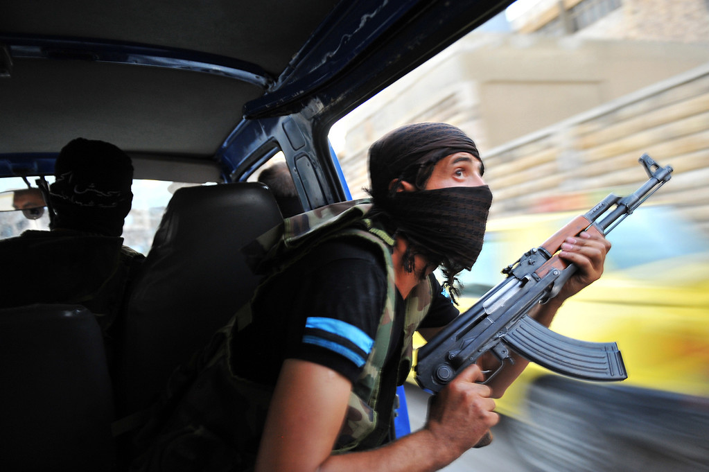 ". Syrian rebels hunt for snipers after attacking the municipality building in the city center of Selehattin, near Aleppo, on July 23, 2012, during fights between rebels and Syrian troops. Syrian rebels ""liberated\"" several districts of the northern city of Aleppo on Monday, a Free Syrian Army spokesman in the country\'s commercial hub said. (BULENT KILIC/AFP/Getty Images)"