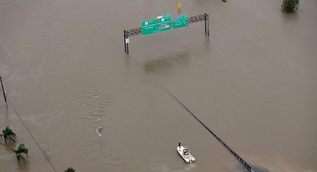 . A boat travels along Interstate 10 as floodwaters from Tropical Storm Harvey cover a portion of the highway Tuesday, Aug. 29, 2017, in Houston. (AP Photo/David J. Phillip)