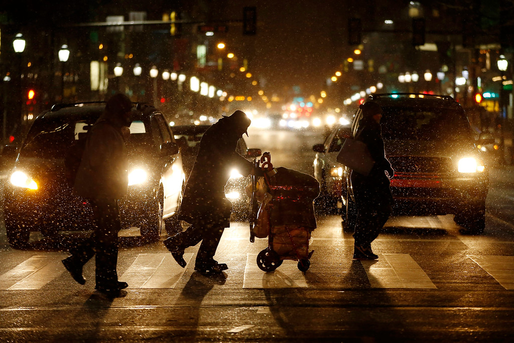 . People walk across Market Street in Philadelphia as snow falls during the evening commute on Friday, Jan. 22, 2016. The National Weather Service issued a blizzard warning for Philadelphia and its suburbs from 7 p.m. Friday until Sunday morning. (AP Photo/Matt Slocum)