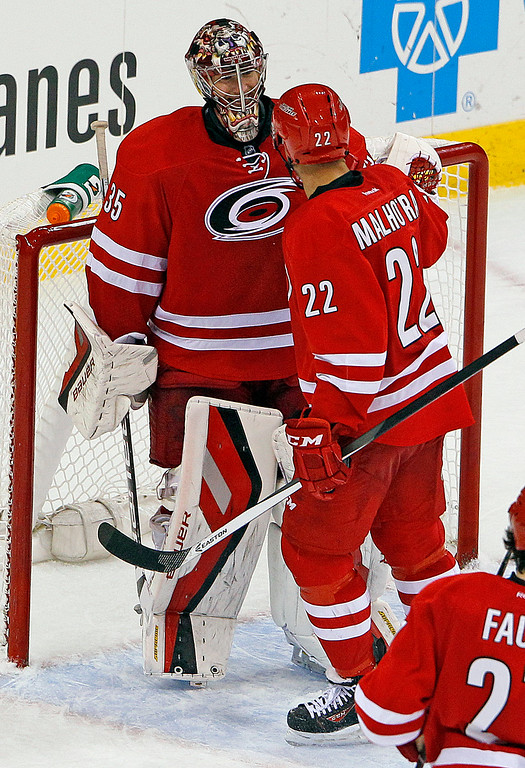. Carolina Hurricanes goalie Justin Peters (35) is congratulated by teammate Manny Malhotra (22) following the Hurricanes 2-1 win against the Colorado Avalanche in Raleigh, N.C., Tuesday, Nov. 12, 2013. (AP Photo/Karl B DeBlaker)