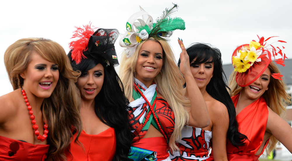 . Racegoers line up for photographers as they attend Ladies Day, the second day of the Grand National Meeting horse racing event at Aintree Racecourse in Liverpool, north-west England on April 5, 2013. The annual three day meeting culminates in the Grand National which is run over a distance of four miles and four furlongs (7,242 metres), and is the biggest betting race in the United Kingdom.  ANDREW YATES/AFP/Getty Images