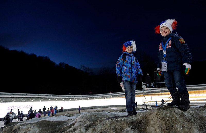 . Children wait for the start of the final run during the men\'s doubles luge at the 2014 Winter Olympics, Wednesday, Feb. 12, 2014, in Krasnaya Polyana, Russia. (AP Photo/Natacha Pisarenko)