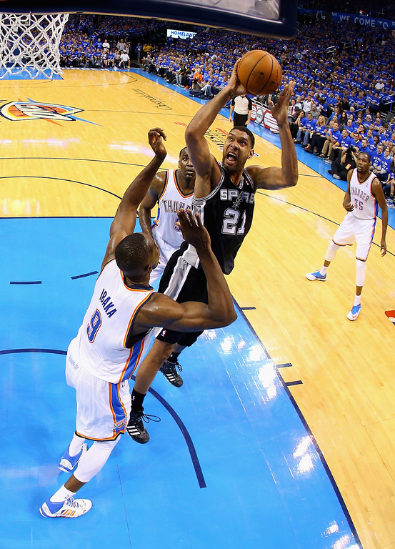 . OKLAHOMA CITY, OK - MAY 25: Tim Duncan #21 of the San Antonio Spurs drives to the basket against Serge Ibaka #9 of the Oklahoma City Thunder in the second half during Game Three of the Western Conference Finals of the 2014 NBA Playoffs at Chesapeake Energy Arena on May 25, 2014 in Oklahoma City, Oklahoma.  (Photo by Ronald Martinez/Getty Images)