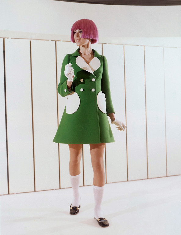 . Green woolen coat with round pockets and white reverse was shown by the Andre Courages fashion house during the Paris Spring and Summer showings in 1969. Buttons are white and the wears a bright colored wig, White cotton socks and black leather flat holed shoes. (AP Photo)