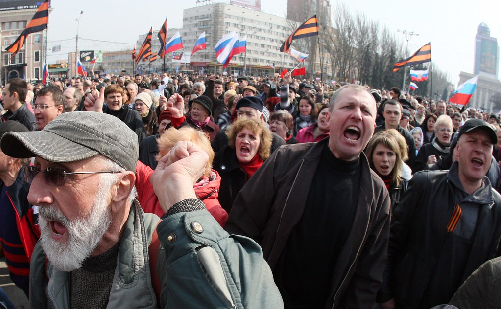 """. Pro-Russian activists shout slogans and hold Russian national flags during a demonstration rally in the center of the eastern Ukrainian city of Donetsk on March 15, 2014. The second successive day of deadly unrest that has now claimed three lives in the mainly Russian-speaking east came hours after Moscow -- its forces already in control of Crimea and conducting snap drills at Ukraine\'s eastern border -- warned that it reserved the right to \""""protect\"""" compatriots throughout its neighbor. AFP PHOTO / ALEXANDER KHUDOTEPLY/AFP/Getty Images"""
