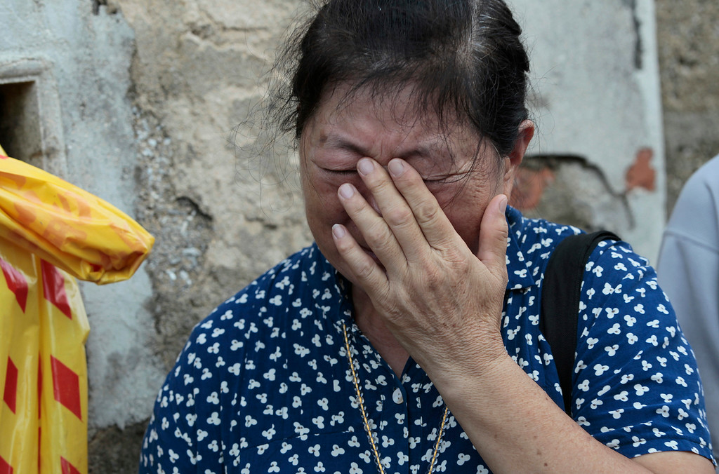 . A relative of a victim killed in the TransAsia Airways flight GE222 crash cries at a makeshift altar at the crash site on the outlying island of Penghu, Taiwan, Thursday, July 24, 2014.  (AP Photo/Wally Santana)