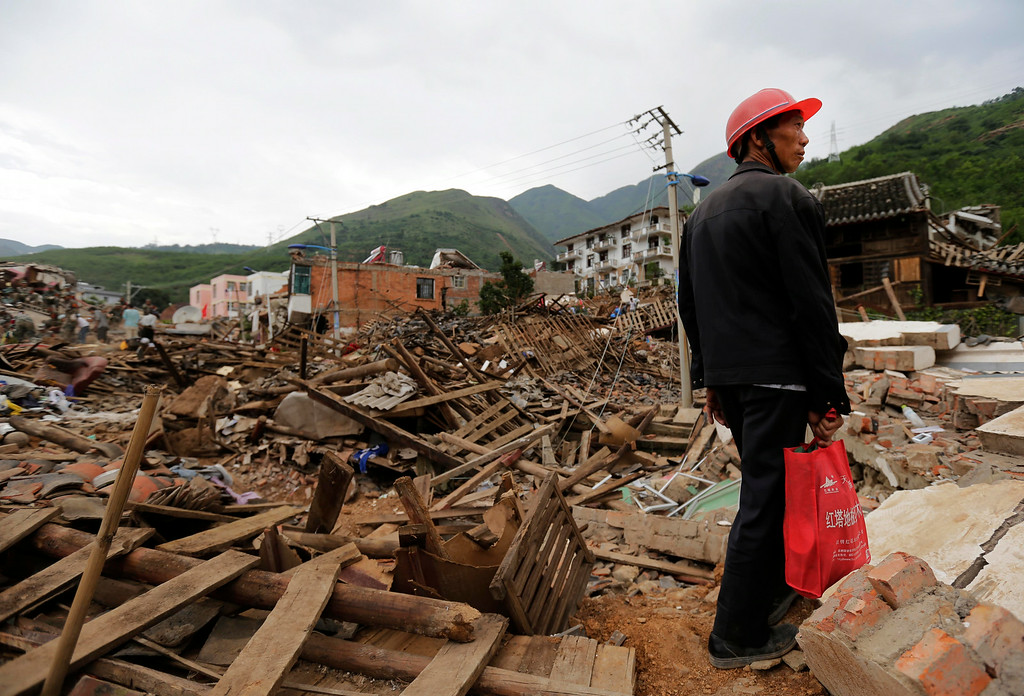 . A villager stands at the rubbles following a massive earthquake in the town of Longtoushan in Ludian County in southwest China\'s Yunnan Province Tuesday, Aug. 5, 2014. (AP Photo/Andy Wong)