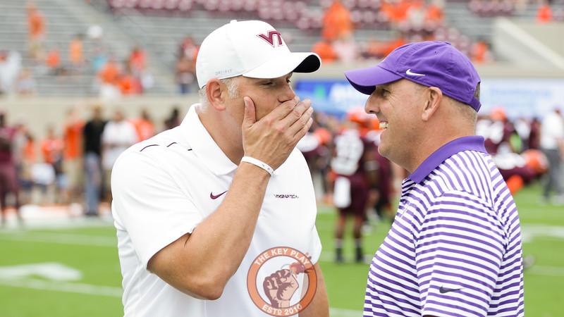 Virginia Tech head coach Justin Fuente (left) speaks with Furman head coach Clay Hendrix (right) at midfield during pre-game warmups. (Mark Umansky/TheKeyPlay.com)