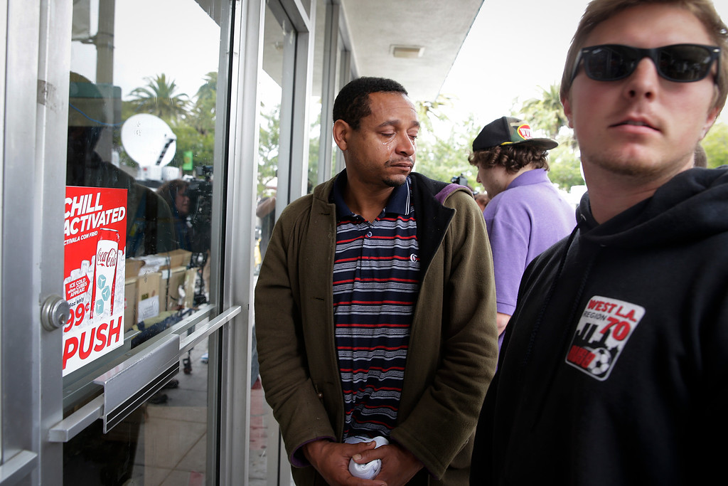 . UC Santa Barbara student Derrick Hayes, center, sheds tears in front of  IV Deli Mark where Friday night\'s mass shooting took place by a drive-by shooter on Saturday, May 24, 2014, in Isla Vista, Calif. The shooter went on a rampage near a Santa Barbara university campus that left seven people dead, including the attacker, and others wounded, authorities said Saturday. (AP Photo/Jae C. Hong)