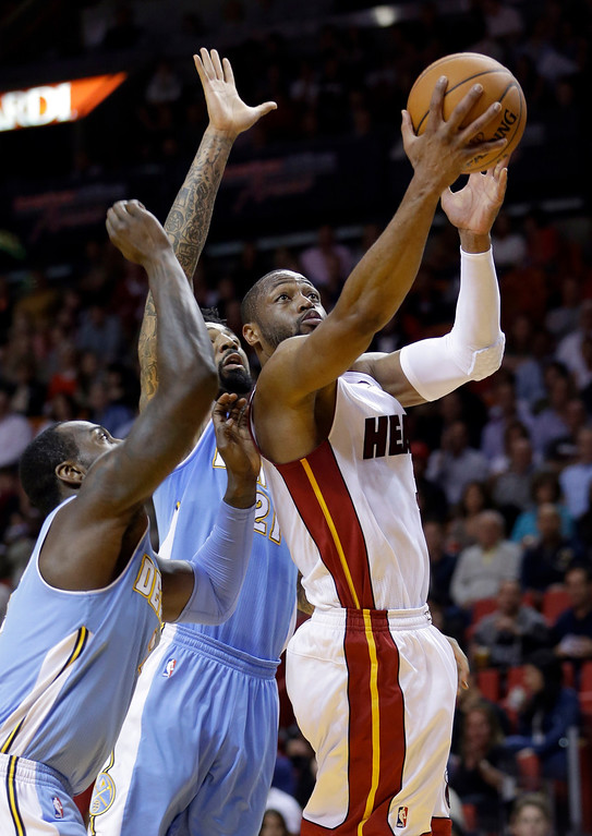 . Miami Heat guard Dwyane Wade (3) prepares to shoot against Denver Nuggets forward Wilson Chandler (21) and J.J. Hickson, left, during the first  half of an NBA basketball game in Miami, Friday, March 14, 2014. (AP Photo/Alan Diaz)