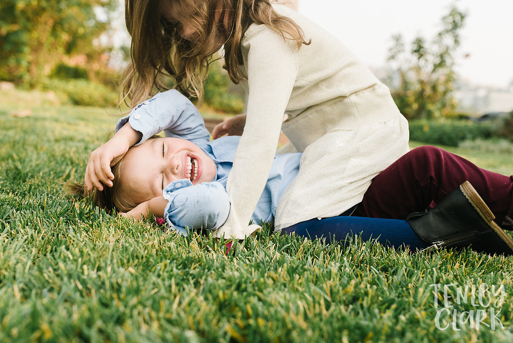 Sibling tackle in backyard grass. Lifestyle in-home family photoshoot in Marin, CA by Tenley Clark Photography.