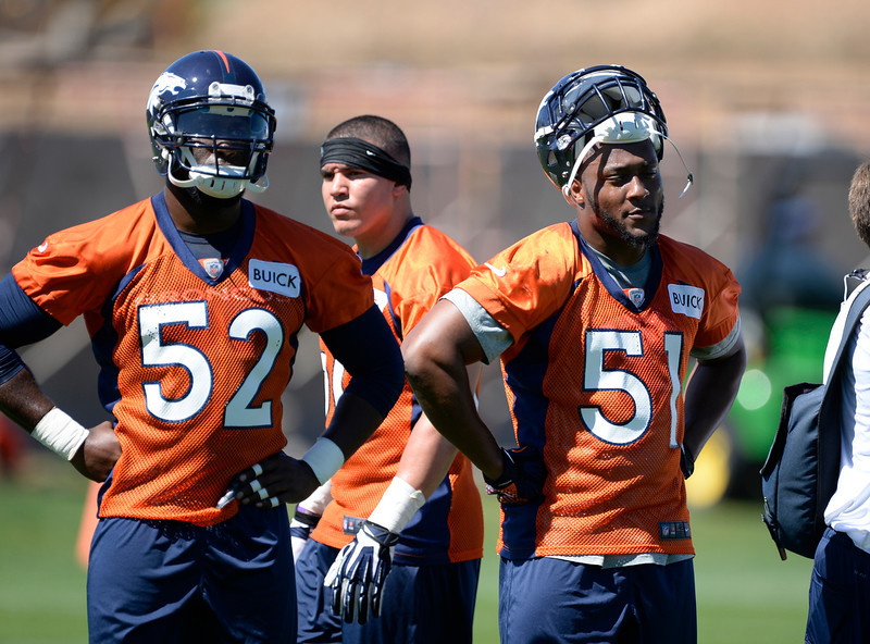 . Denver Broncos Jerrell Harris (52) and Jamar Chaney (51) look on during practice May 28, 2014 at Dove Valley. (Photo by John Leyba/The Denver Post)