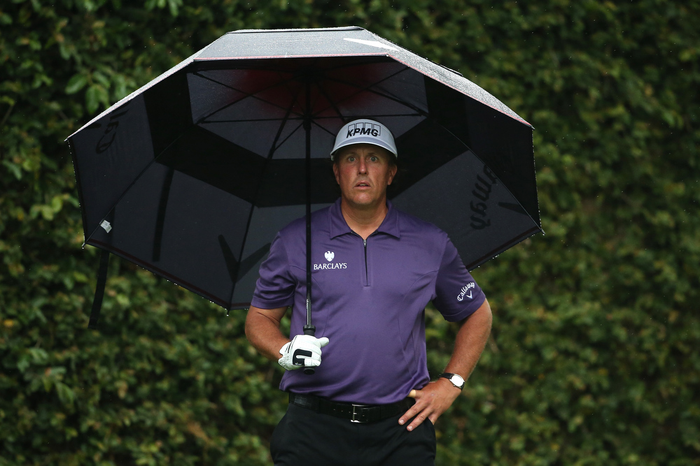Description of . Phil Mickelson of the United States stands under an umbrella on the second tee during the second round of the 2013 Masters Tournament at Augusta National Golf Club on April 12, 2013 in Augusta, Georgia.  (Photo by Andrew Redington/Getty Images)