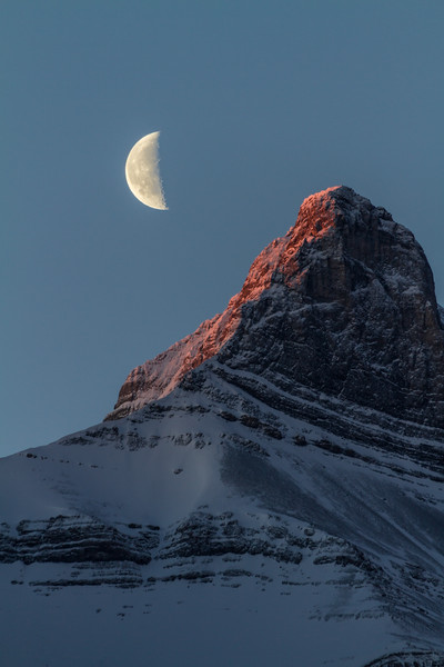A half moon begins to set behind a towering, snow-covered mountain in Canmore, Alberta, Canada