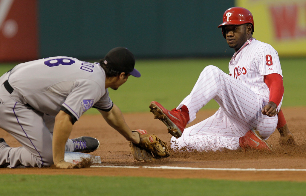 . Philadelphia Phillies\' Domonic Brown (9) is safe at third before Colorado Rockies third baseman Nolan Arenado can make the tag in the second inning in a baseball game, Thursday, Aug. 22, 2013, in Philadelphia. (AP Photo/Laurence Kesterson)