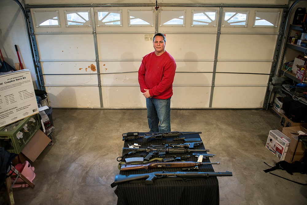 . Patrick Troy, who is a force security instructor with the Blevins\'s preparedness group, poses with firearms including a M1 carbine rifle and an AR-15 rifle December 5, 2012 in Berryville, Virginia. Jay Blevins and his wife Holly Blevins have been preparing with a group of others for a possible doomsday scenario where the group will have to be self sufficient due to catastrophe or civil unrest. BRENDAN SMIALOWSKI/AFP/Getty Images