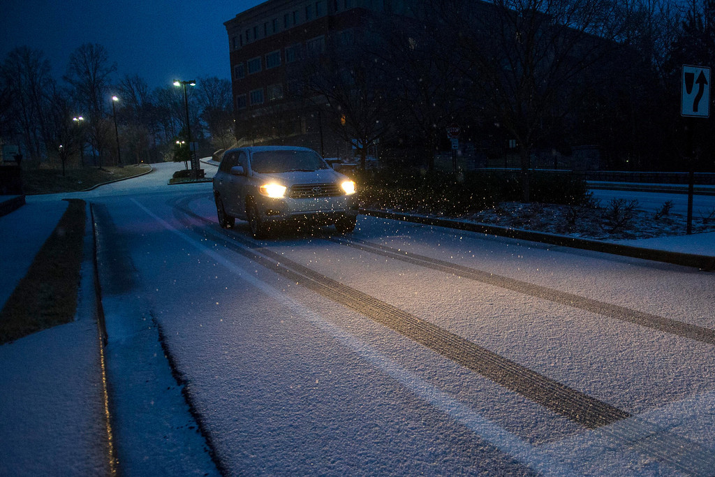 """. A motorist drives on a street covered with snow and ice as a winter storm begins to roll through on Wednesday, Feb. 12, 2014, in Johns Creek, Ga.   Across the South, winter-weary residents woke up Wednesday to a region encased in ice, snow and freezing rain, with forecasters warning that the worst of the potentially \""""catastrophic\"""" storm is yet to come. From Texas to the Carolinas and the South\'s business hub in Atlanta, roads were slick with ice, tens of thousands were without power, and a wintry mix fell in many areas. (AP Photo/John Amis)"""