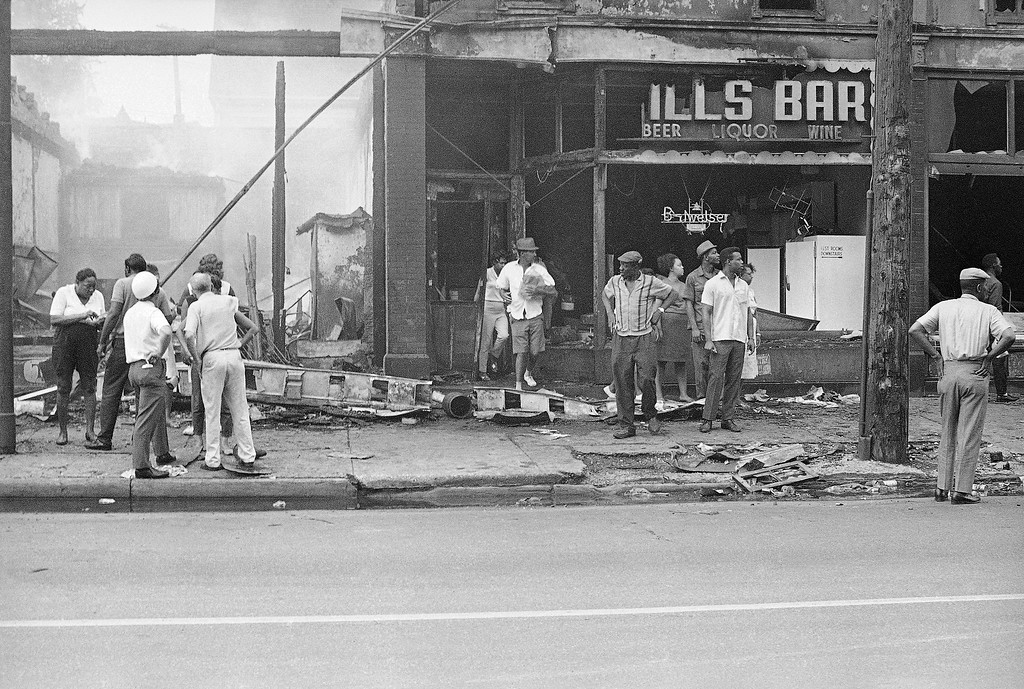 . A man in Bermuda shorts carries loaded bags from a burned-out bar on Hough Avenue in Cleveland, Ohio, July 19, 1966 while a small group of people look up and down the street. The bar was one of several buildings burned during rioting in the predominantly black area last night. (AP Photo/Julian C. Wilson)