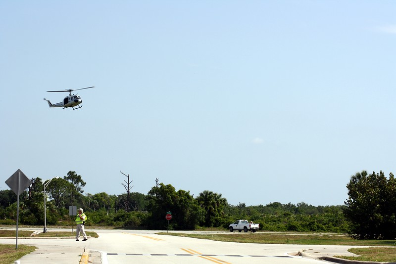 A NASA security helicopter with mounted machine guns hovers over the area where the crew of STS-125 will travel