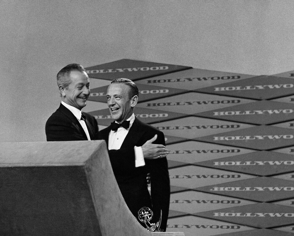 . Dancing star Fred Astaire, who dominated the 11th annual Television Academy awards ceremony by winning an unprecedented nine Emmys, gets a pat on the shoulder from actor Robert Young as Astaire accepted the final statuette. Young, an old friend, dashed from his seat in the Moulin Rouge audience in Hollywood, Los Angeles on May 6, 1959 to present the golden Emmy when Astaire found himself announced on stage for the final Emmy, but with no presenter. He won the multitude of honors for his show ìAN Evening With Fred Astaireî. (AP Photo)