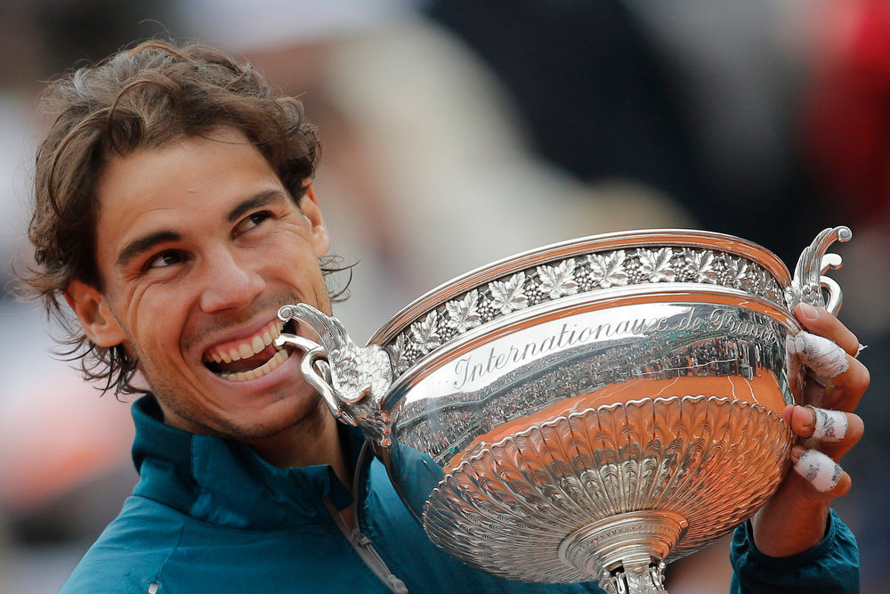 . Spain\'s Rafael Nadal bites the trophy after winning against compatriot David Ferrer in three sets 6-3, 6-2, 6-3, in the final of the French Open tennis tournament, at Roland Garros stadium in Paris, Sunday June 9, 2013. (AP Photo/Christophe Ena)