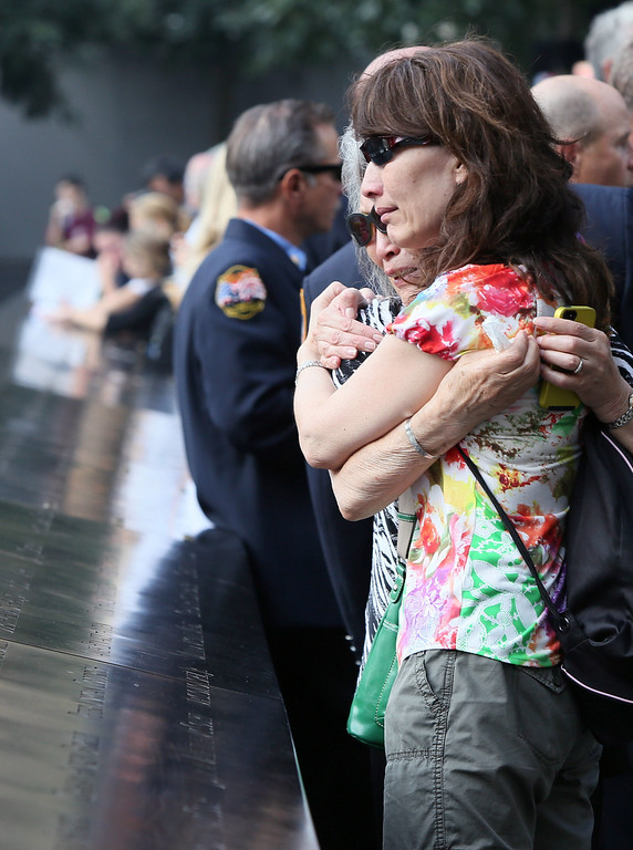 . Mija Quigley of Princeton Junction, NJ embraces her daughter Ruth Quigley Lawrence as they come to see the name of Mija\'s son and Ruth\'s brother Patrick Quigley who died aboard Flight 175, as they attend ceremonies for the twelfth anniversary of the terrorist attacks on lower Manhattan at the World Trade Center site on September 11, 2013 in New York City.  (Photo by Chris Pedota-Pool/Getty Images)