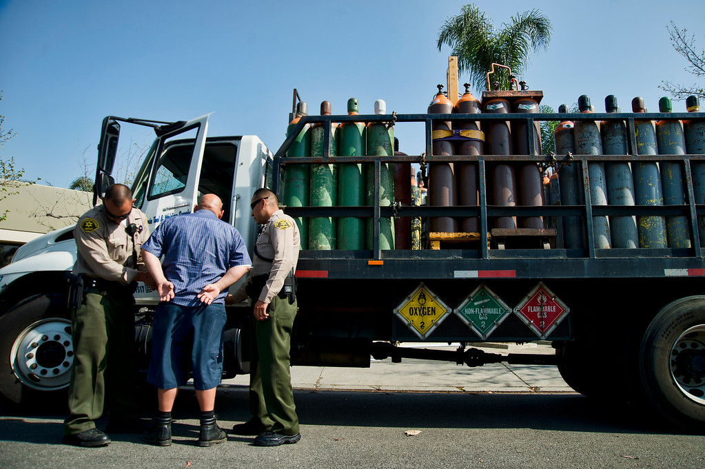 . Los Angeles County Sheriff\'s deputies detain the deliver driver as he prepares to deliver a truck full of nitrous oxide to auto parts dealer, L.A. Rush, during a search warrant in Norwalk on Friday, March 22, 2013. The business is suspected of illegally selling nitrous oxide for recreational drug use. (SGVN/Staff photo by Watchara Phomicinda)