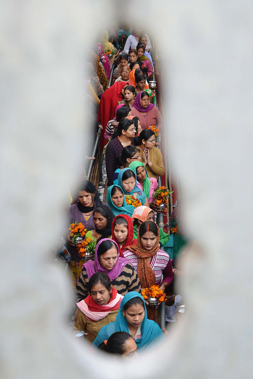 . Indian Hindu devotees wait in line to pay their respects to a Shiva Lingam, a stone sculpture representing the phallus of Lord Shiva, during the Maha Shivaratri festival at the Shivala Temple in Amritsar on February 27, 2014. AFP PHOTO/NARINDER  NANU/AFP/Getty Images