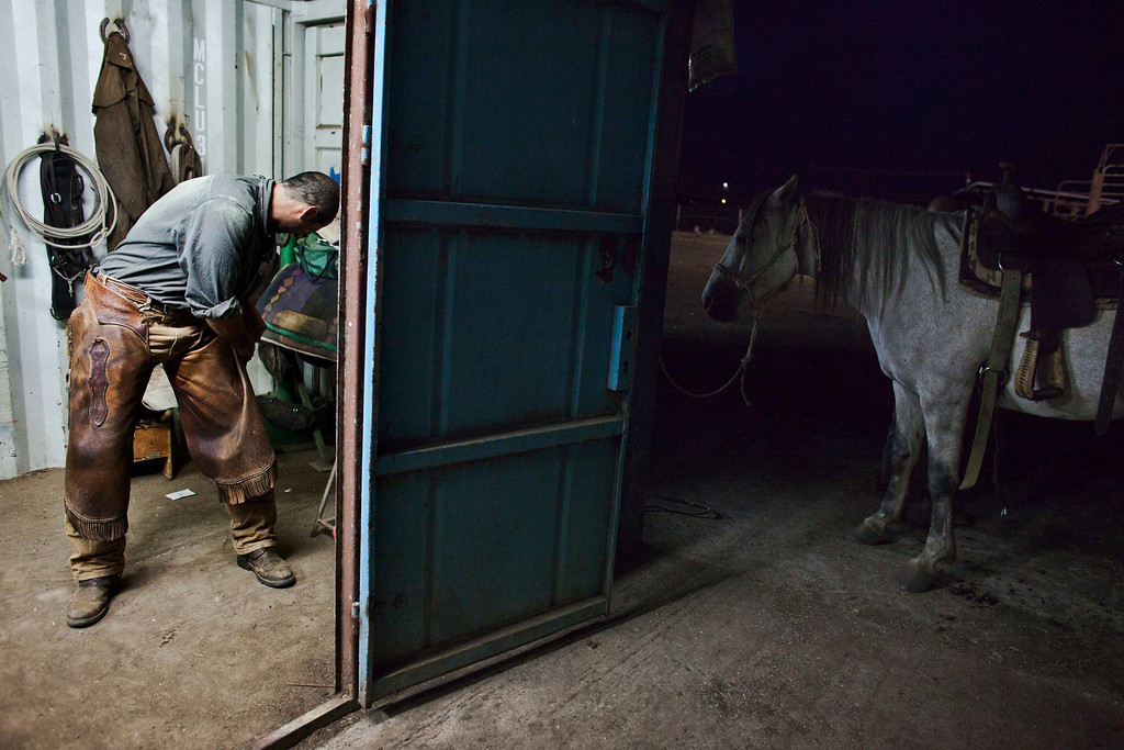 . Amit, an Israeli cowboy, gets dressed for work in the early morning on a ranch just outside Moshav Yonatan, a collective farming community, about 2 km (1 mile) south of the ceasefire line between Israel and Syria in the Golan Heights May 21, 2013. REUTERS/Nir Elias