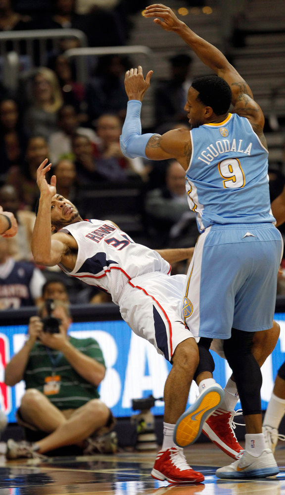 . Atlanta Hawks point guard Devin Harris (34) is fouled by Denver Nuggets shooting guard Andre Iguodala (9) during the first half of an NBA  basketball game on Wednesday, Dec. 5, 2012, in Atlanta. (AP Photo/John Bazemore)