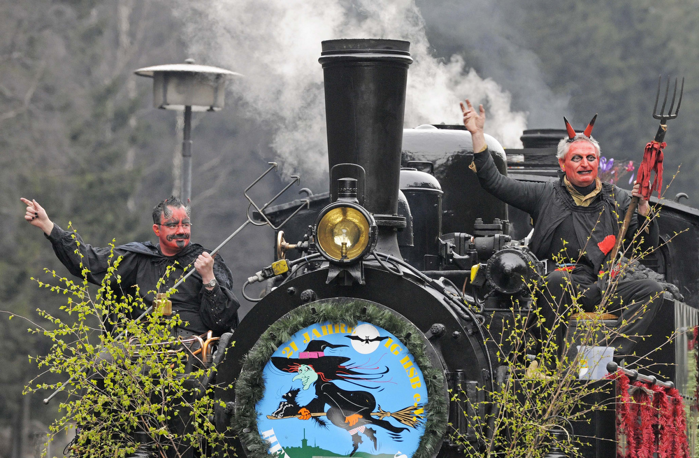 . Men costumed as devils pose in front of a steam engine of a small train in Schierke, central Germany, Tuesday, April 30, 2013. Hundreds of costumed devils and witches meet to celebrate Walpurgis Night, a traditional religious holiday of pre-Christian origins. The event is named after St. Walburga, an English nun who helped convert the Germans to Christianity in the 8th century. (AP Photo/Jens Meyer)