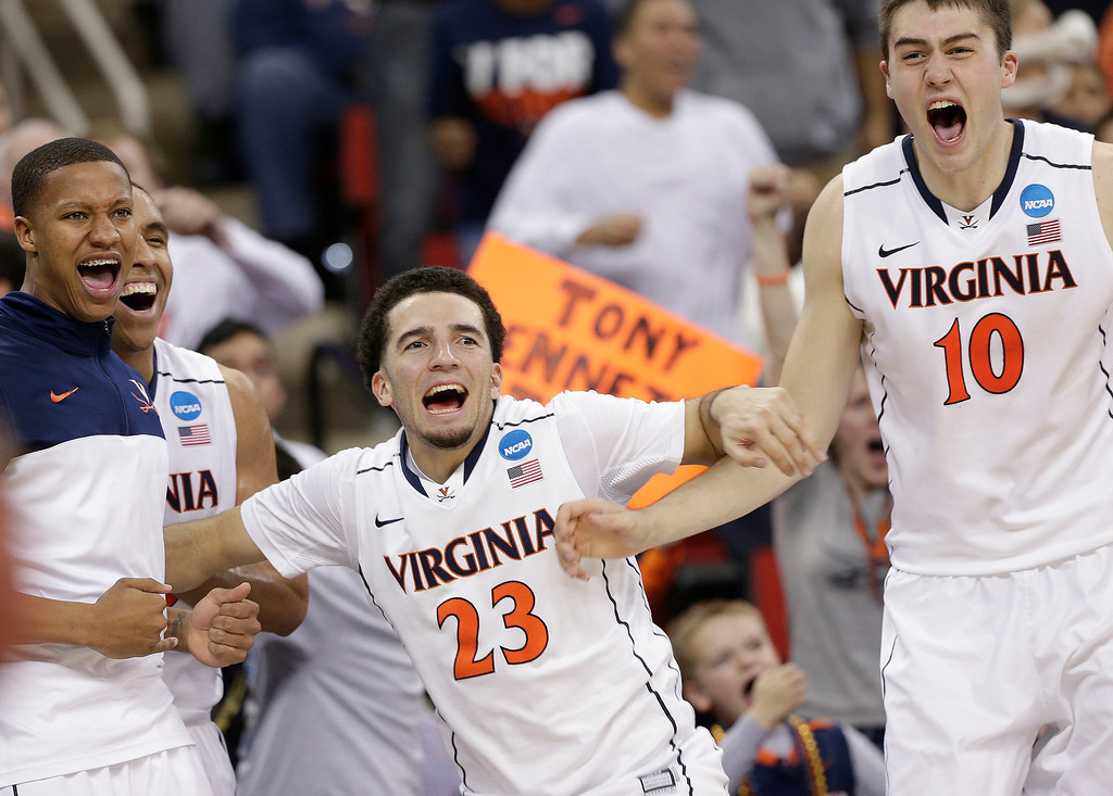 . Virginia\'s  London Perrantes (23) Mike Tobey (10) and other players celebrate after the second half of an NCAA college basketball third-round tournament game against Memphis, Sunday, March 23, 2014, in Raleigh, N.C. Virginia won 78-60. (AP Photo/Chuck Burton)