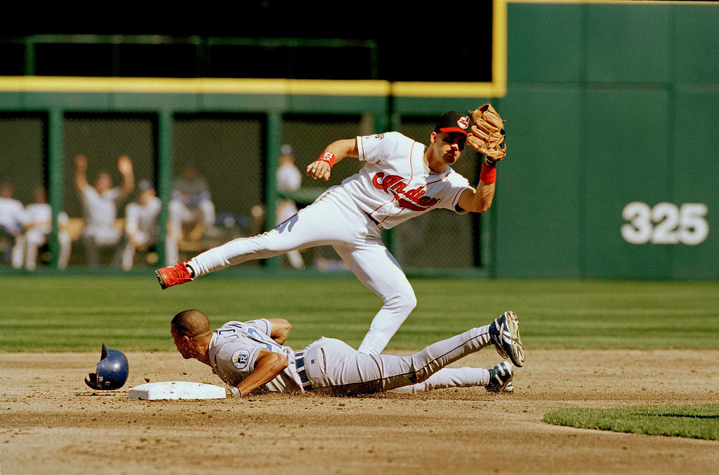 . Cleveland Indians\' shortstop Omar Visquel, right, skips over sliding Kansas City Royals runner Tom Goodwin after Goodwin was caught stealing second base in the fourth inning in Cleveland, Ohio, Sept. 30, 1995. (AP Photo/Mark Duncan)
