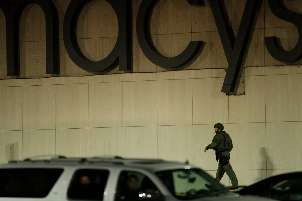 . An official wearing tactical gear walks outside of the Garden State Plaza Mall following reports of a shooter, Monday, Nov. 4, 2013, in Paramus, N.J. Hundreds of law enforcement officers converged on the mall Monday night after witnesses said multiple shots were fired there. (AP Photo/Julio Cortez)