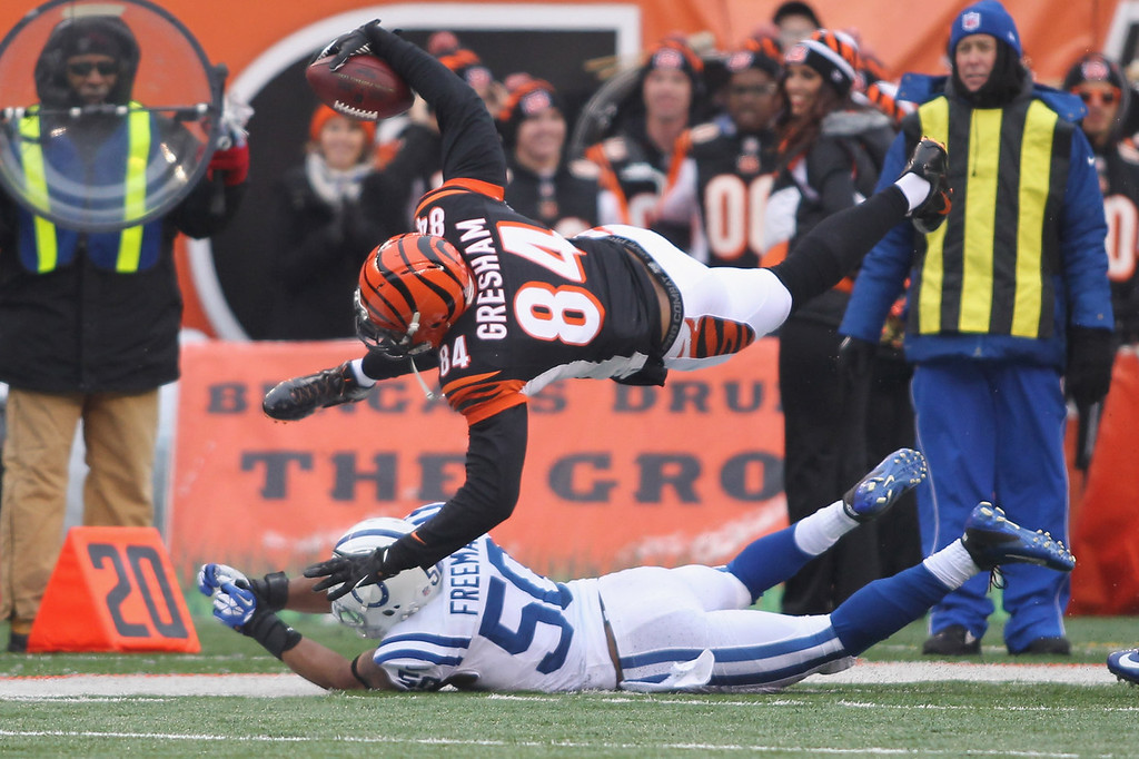 . Jermaine Gresham #84 of the Cincinnati Bengals runs the ball upfield over a diving Jerrell Freeman #50 of the Indianapolis Colts during their game against the Indianapolis Colts at Paul Brown Stadium on December 8, 2013 in Cincinnati, Ohio.  (Photo by John Grieshop/Getty Images)