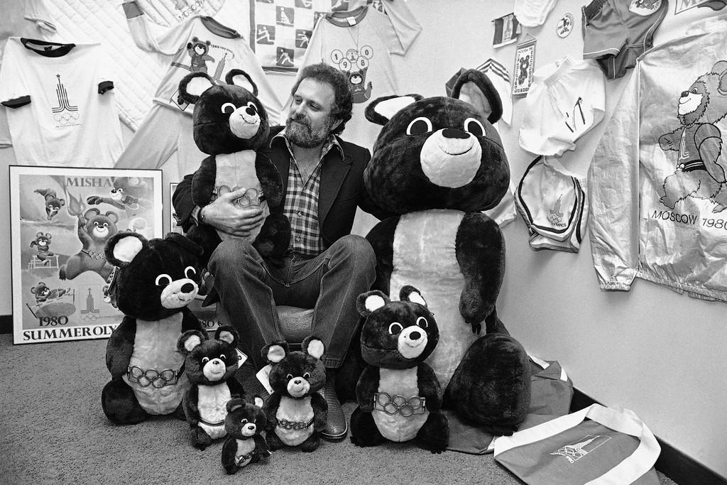 """. Los Angeles businessman Stanford Blum sits with some of the items featuring Mischa, the official mascot for the 1980 summer Olympics in Moscow, which his company has marketing rights on. Blum said in an interview in Los Angeles, Jan. 24, 1980 that sales of Mischa materials has almost stopped, a victim of recent tensions between the United States and Soviet Union. \""""As of now, Mischa the bear is dead.\"""" Blum said. (AP Photo/Wally Fong)"""
