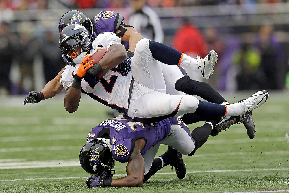 . Denver Broncos running back Knowshon Moreno is stopped by Baltimore Ravens inside linebacker Brendon Ayanbadejo, top, and defensive back James Ihedigbo, bottom during the first half of an NFL football game in Baltimore, Sunday, Dec. 16, 2012. (AP Photo/Patrick Semansky)
